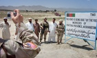 In this 2005 photo, U.S. military operational commander in Afghanistan, Maj. Gen. Jason Kamiya, right, poses with Afghan workers and a U.S. soldier for a photo in a U.S. military-funded road through Urgun town in Paktika province, eastern Afghanistan.
