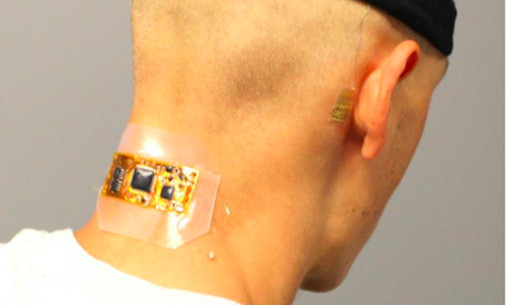 Test subject who has flexible wireless electronics conformed to the back of the neck, with dry hair electrodes under a fabric headband and a membrane electrode on the mastoid, connected with thin-film cables.