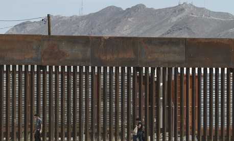 In this July 17, 2019, file photo, three migrants who had managed to evade the Mexican National Guard and cross the Rio Grande onto U.S. territory walk along a border wall set back from the geographical border, in El Paso, Texas