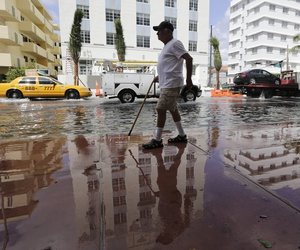 A man walks along a flooded street in Miami Beach, Fla.