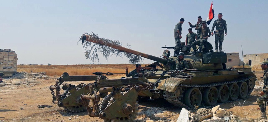 In this Tuesday, Aug. 13, 2019 photo, released by the Syrian official news agency SANA, Syrian army soldiers flash the victory sign as they stand on a tank, in northwestern Syria.