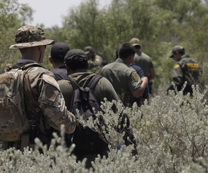 Four people apprehended by members of the U.S. Border Patrol Search, Trauma, and Rescue (BORSTAR) team are led to awaiting vehicles near Eagle Pass, Texas in June.