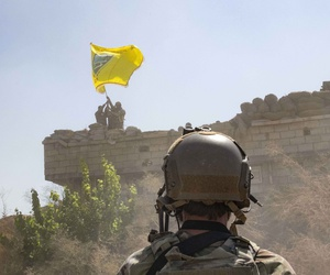 "In this Sept. 21, 2019, photo,  a U.S. soldier watches the Syrian Democratic Forces demolish a Kurdish fighters' fortification and raise a Tal Abyad Military Council flag over the outpost as part of the so-called ""safe zone"" near the Turkish border."