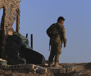 A fighter from the Syrian Democratic Forces, SDF, stands inside a post where U.S. troops were based, in Tel Abyad town, at the Syrian-Turkish border, Syria, Monday, Oct. 7, 2019.