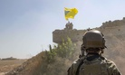 "A U.S. soldier oversees members of the Syrian Democratic Forces, or SDF, demolishing a Kurdish fighters' fortification and raising a Tal Abyad Military Council flag as part of the ""safe zone"" near the Turkish border, Sept. 21, 2019."