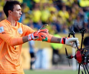 Uruguay's goalkeeper Fernando Muslera picks up a drone which landed on the field during a 2018 World Cup qualifying soccer match in Quito, Ecuador, Thursday, Nov. 12, 2015.