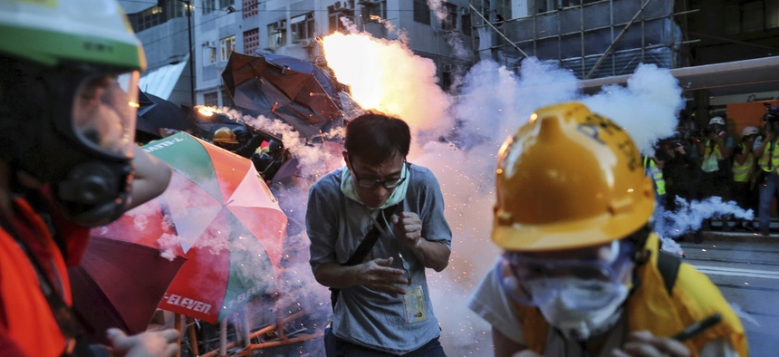 Protesters and journalists react to tear gas fired into a crowd on the streets of Hong Kong on Sunday, July 28, 2019.