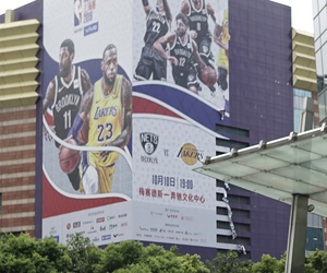 An official directs traffic near a Chinese flag and a billboard advertising an NBA preseason basketball game on Thursday between the Los Angeles Lakers and Brooklyn Nets in Shanghai, China, Wednesday, Oct. 9, 2019.