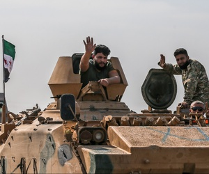 Turkish-backed Syrian opposition fighters on an armoured personnel carrier wave as they drive to cross the border into Syria, in Akcakale, Sanliurfa province, southeastern Turkey, on Friday.