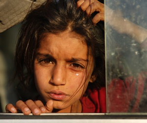 A Syrian girl who is newly displaced by the Turkish military operation in northeastern Syria, weeps as she sits in a bus upon her arrival at the Bardarash camp, north of Mosul, Iraq, Wednesday, Oct. 16, 2019.