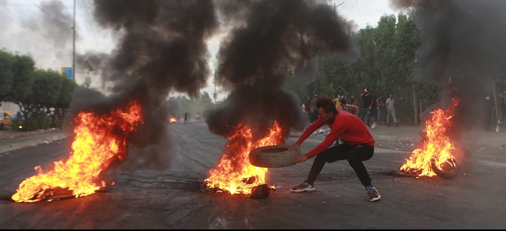 Anti-government protesters set fires and close a street during a demonstration in Baghdad, Iraq, Sunday, Oct. 6, 2019.