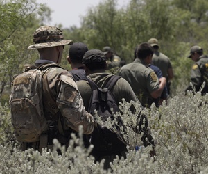 Four migrants are apprehended in dense brush by members of the U.S. Border Patrol Search, Trauma, and Rescue (BORSTAR) team are led to awaiting vehicles near Eagle Pass in June.