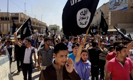In this June 16, 2014 file photo, demonstrators chant pro-Islamic State group, slogans as they carry the group's flags in front of the provincial government headquarters in Mosul, Iraq.