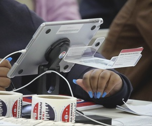 A new E-Poll Book tablet is used to process a voter, during early voting at Brooklyn's Clara Barton High School, Saturday Oct. 26, 2019, in New York.