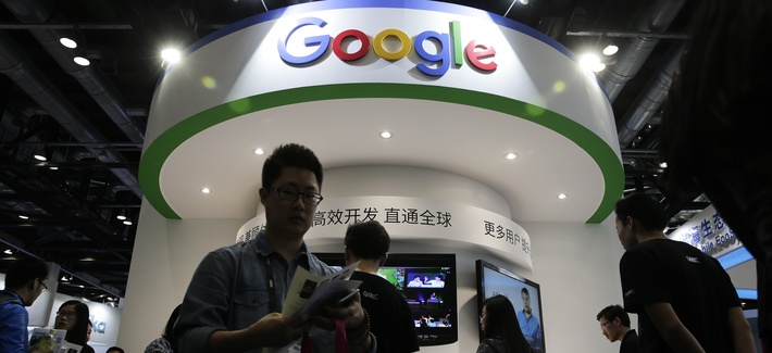 In this April 28, 2016, file photo, visitors gather at a display booth for Google at the 2016 Global Mobile Internet Conference (GMIC) in Beijing.