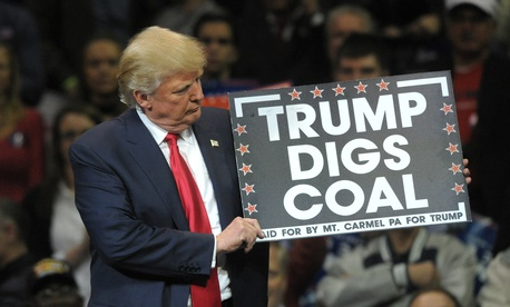Republican Presidential nominee Donald Trump holds a 'Trump Digs Coal' sign during a rally Oct. 10, 2016, at Mohegan Sun Arena in Wilkes-Barre, Pennsylvania