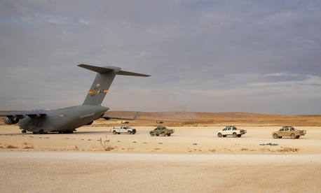 In this Oct. 25, 2019, photo, pickup trucks line up to be loaded onto a cargo plane at the Kobani Landing Zone (KLZ), part of  coalition forces' withdrawal from northern Syria.