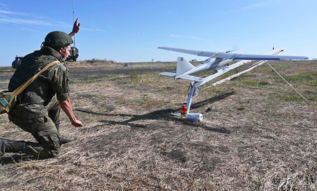 A Russian soldier launching an Orlan-10 drone