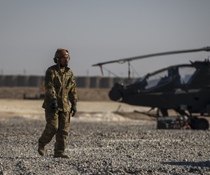 A crewman walks past an attack helicopter at a US military base at an undisclosed location in eastern Syria, Monday, Nov. 11, 2019.