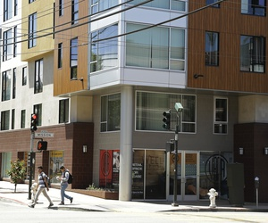 Two men walk past a new apartment building on Mission Street Tuesday, June 2, 2015, in San Francisco.