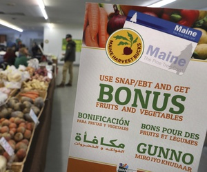 In this Friday, March 17, 2017, file photo, a sign advertises a program that allows food stamp recipients to use their EBT cards to shop at a farmer's market in Topsham, Maine.