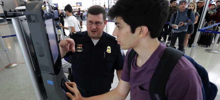 U.S. Customs and Border Protection supervisor Erik Gordon, left, helps passenger Ronan Pabhye navigate a facial recognition kiosk at Houston's George Bush Intercontinental Airport.