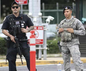 Security stands guard Wednesday outside the main gate at Joint Base Pearl Harbor-Hickam in Hawaii.