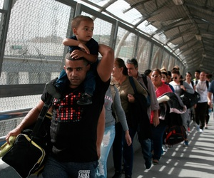 Cuban migrants are escorted by Mexican immigration officials in Ciudad Juarez, Mexico, as they cross the Paso del Norte International bridge to be processed as asylum seekers on the U.S. side of the border.