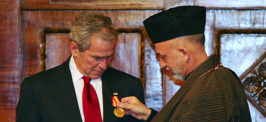 Afghan President Hamid Karzai, right, gives a medal to U.S. President George W. Bush at the presidential palace in Kabul, Afghanistan on Monday, Dec. 15, 2008.Afghan President Hamid Karzai, right, gives a medal to U.S. President George W. Bush at the pres