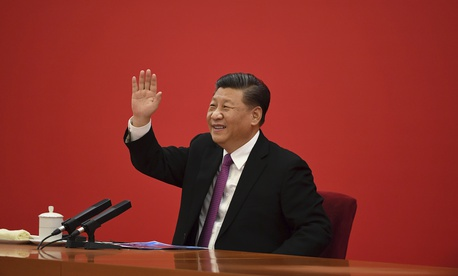 China's President Xi Jinping waves to Russian President Vladimir Putin via a video link, from the Great Hall of the People in Beijing, Monday, Dec. 2, 2019.
