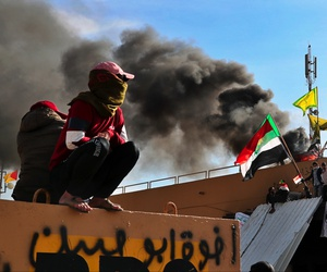 Pro-Iranian militiamen and their supporters set a fire during a sit-in in front of the U.S. embassy in Baghdad, Iraq, Wednesday, Jan. 1, 2020.