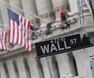 The Wall St. street sign is framed by American flags flying outside the New York Stock Exchange, Friday, Jan. 3.