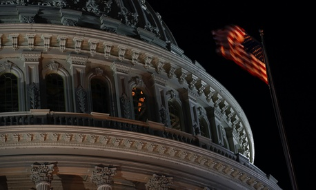 An American flag flutters in the wind in front of the U.S. Capitol dome in Washington, late Tuesday, Nov. 12, 2019.