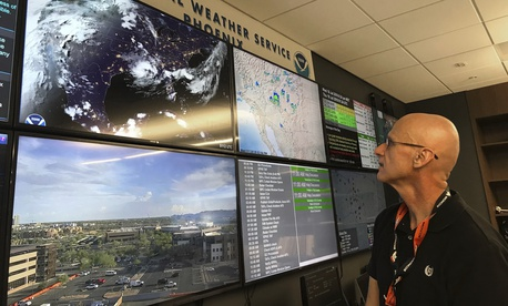 n this Wednesday, July 18, 2018 photo, National Weather Service forecaster Marvin Percha reviews monitors that track satellite and Doppler radar images, as well as his colleagues' forecasts posted on social media, at Tempe, AZ.