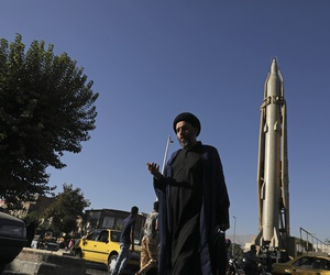 A Muslim cleric walks in downtown Tehran, where a Shahab-3 surface-to-surface missile is on display on Sept. 25, 2019.