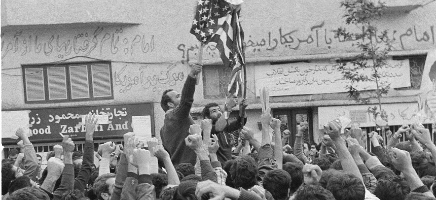 An Iranian protestor sets fire to a U.S. flag while other demonstrators clench their fists during an anti-American protest in Tehran, Nov. 5, 1979.