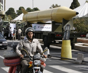 Iranians drive next to a Shahab-3 ballistic missile, which is displayed in an equipment display by the Iranian Revolutionary Guard marking the 30th anniversary of the outset of the1980-88 Iran-Iraq war, at Baharestan Square in Tehran, Iran, in 2010.