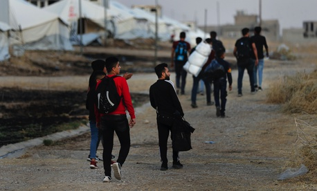 Syrians who were displaced by the Turkish military operation in northeastern Syria carry their belongings as they arrive at the Bardarash refugee camp, north of Mosul, Iraq, Thursday, Oct. 17, 2019.