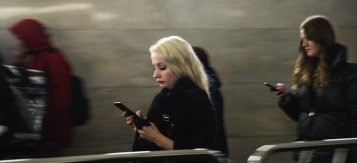 Women use their smartphones wile walking in Moscow's subway, Russia, Monday, Dec. 23, 2019.