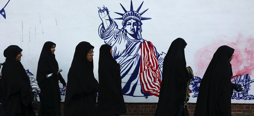 Mourners walk back from a funeral ceremony for Iranian Gen. Qassem Soleimani, passing a satirical drawing of the Statue of Liberty painted on the wall of the former U.S. Embassy in Tehran, Iran, Monday, Jan. 6, 2020.