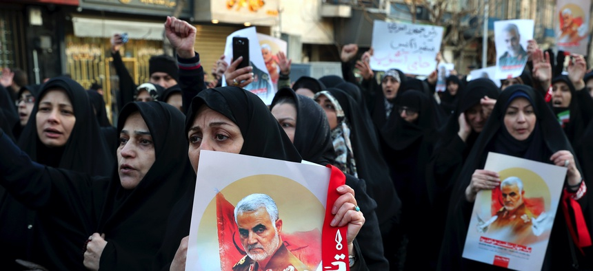Protesters chant slogans while holding up posters of Gen. Qassem Soleimani during a demonstration in front of the British Embassy in Tehran, Iran, Sunday, Jan. 12, 2020.