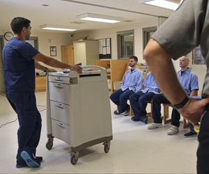 In this July 23, 2018, photo, inmates at Franklin County Jail in Massachusetts are watched by nurse Brian Toia, left, and a corrections officer after they received their daily doses of buprenorphine, a drug which controls heroin and opioid cravings.