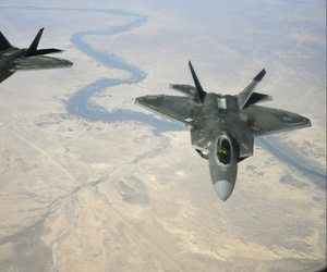 U.S. Air Force F-22 Raptors fly in formation behind a 28th Expeditionary Air Refueling Squadron KC-135 Stratotanker during a combat air patrol mission, Nov. 15, 2019.