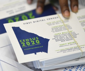 In this Aug. 13, 2019, file photo a worker gets ready to pass out instructions in how fill out the 2020 census during a town hall meeting in Lithonia, Ga.