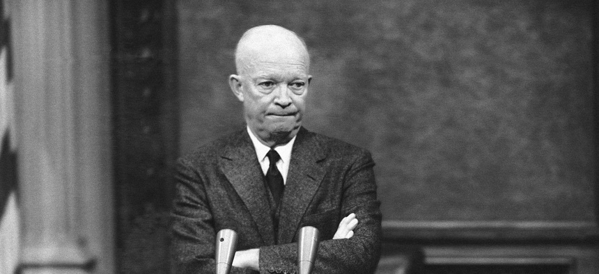 President Dwight Eisenhower, tight- lipped and standing with folded arms, is thoughtful in Washington, D.C., Jan. 19, 1956.