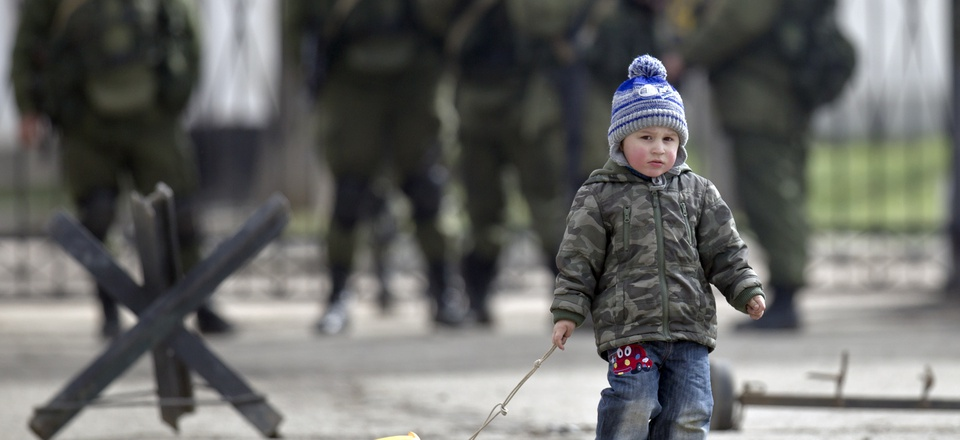 A child drags a toy truck past pro-Russian soldiers standing outside an Ukrainian military base in Perevalne, Crimea, Thursday, March 20, 2014.