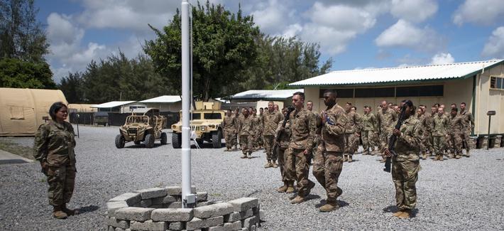 In this photo taken Aug. 26, 2019 and released by the U.S. Air Force, airmen from the 475th Expeditionary Air Base Squadron conduct a flag-raising ceremony, signifying the change from tactical to enduring operations, at Camp Simba, Manda Bay, Kenya.
