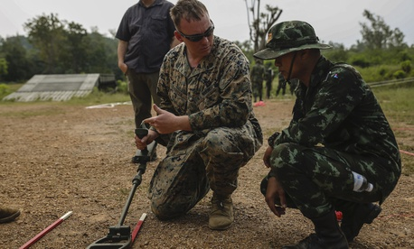 U.S. Marine Corps Staff Sgt. Gabriel T. Green, a platoon sergeant with 9th assists Thai soldiers with a metal detector during survey training event at the Charumanee Training Field in Ratchaburi, Kingdom of Thailand, Dec. 18, 2018.