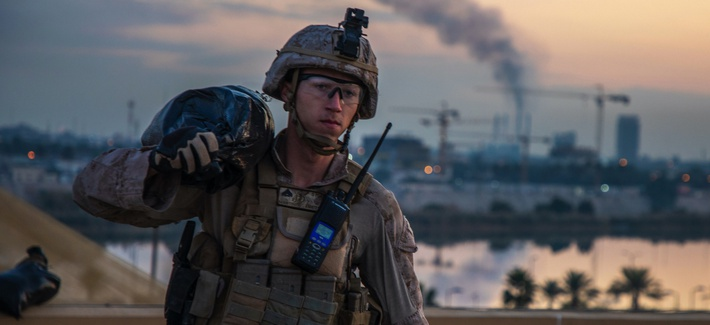 A US Marine carries a sandbag to strengthen a security post during the reinforcement of the Baghdad Embassy Compound in Iraq, Jan. 4, 2020.