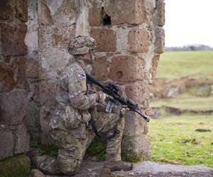 A U.S. Army paratrooper simulates providing security during a mock airborne assault in Monte Romano, Italy, Jan. 29, 2020.